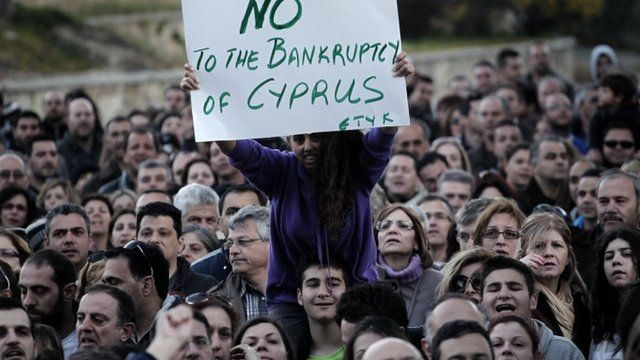 """Woman sitting on shoulders of protester, holding sign saying """"No to the bankruptcy of Cyprus"""""""