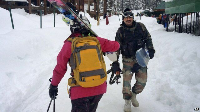 Indian Army soldier carries a snowboard and an automatic rifle as he walks past a skier below the gondola at Gulmarg, Kashmir