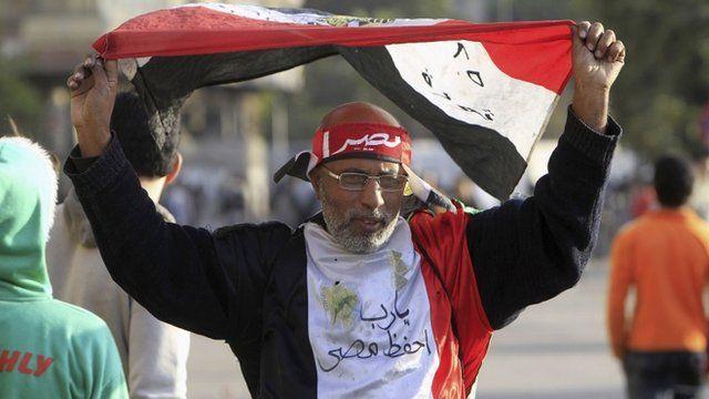A protester opposing Egyptian President Mohamed Mursi's rule waves an Egyptian flag