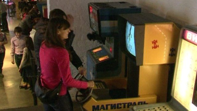A visitor playing a racing game on a soviet-era arcade machine