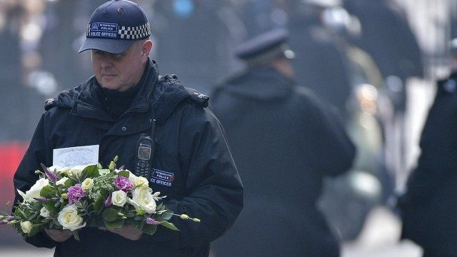 Police officer carries flowers into Downing Street