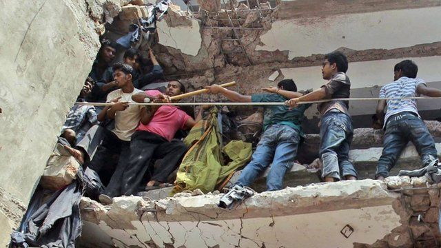 Bangladeshi rescuers squeeze through a gap to help pull out survivors spotted in the debris of a building that collapsed in Savar, near Dhaka