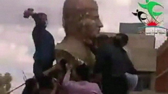 A still from unverified amateur footage apparently shows a statue of Syrian leader Bashar al-Assad's father being attacked