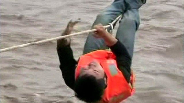 A man hangs on a rope above the flood water