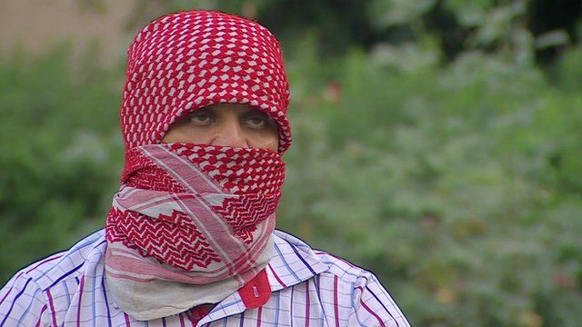 Man with face covered describes recruiting Shia Iraqis to fight alongside Syrian forces