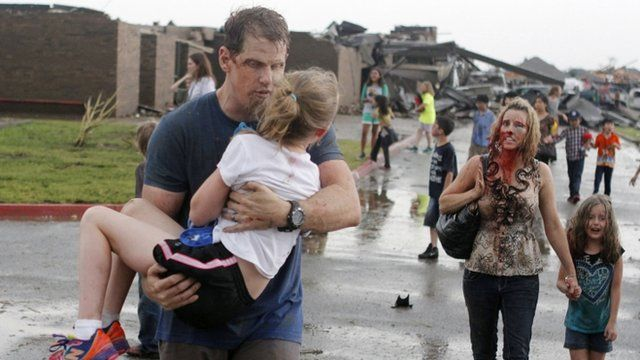 The Cobb family walk away from the tornado aftermath in Oklahoma