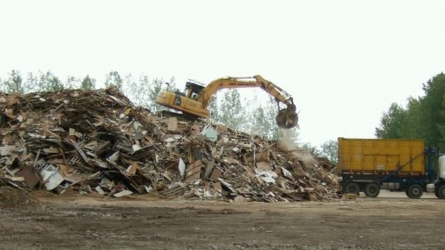 A mechanical digger on a pile of industrial waste