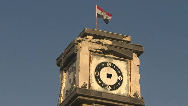 The Syrian flag and a picture of President Assad flies on top of Qusayr's clock tower