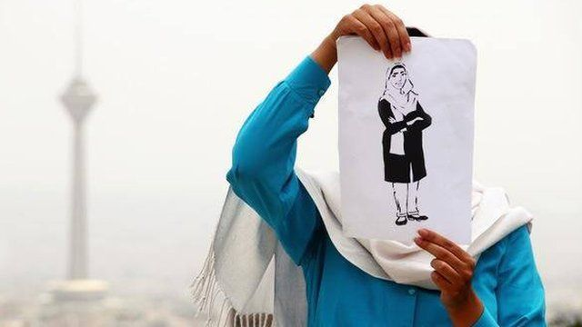 A woman holding a drawing of Zahra