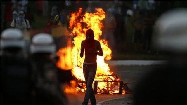 A protester walks in front of a burning barricade in Salvador