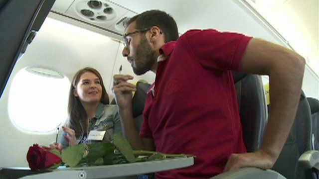 A man and a woman speed-dating on a plane