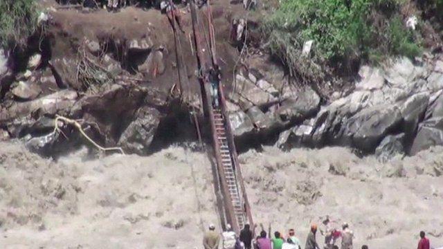 People cross water on bridge