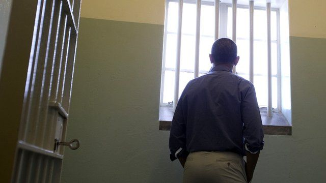 U.S. President Barack Obama U.S. peers out from Section B, prison cell No. 5, on Robben Island, South Africa, Sunday, June 30, 2013.