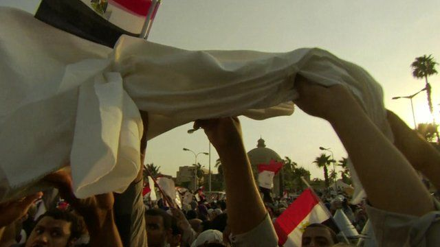 : Young Egyptian men wave death shrouds