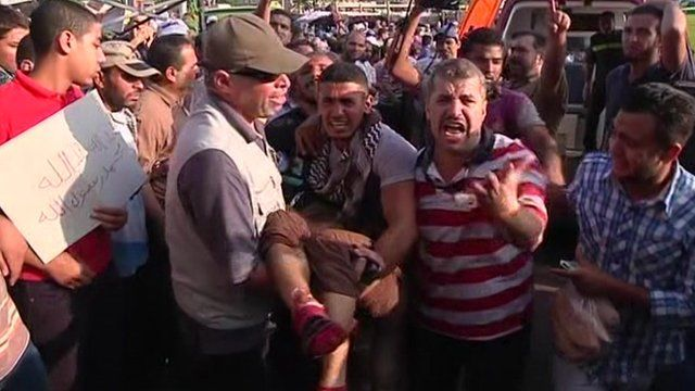 An injured man being carried through the crowd