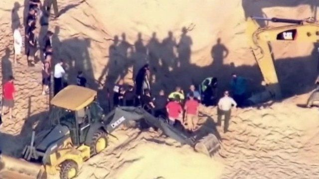 Rescuers and diggers at sand dune