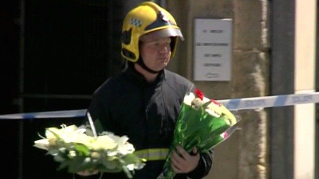 Fireman carrying floral tributes