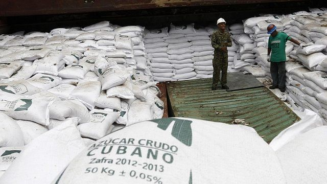 "Workers stand on top of bags labelled ""Cuban raw sugar"" inside a North Korean flagged ship"