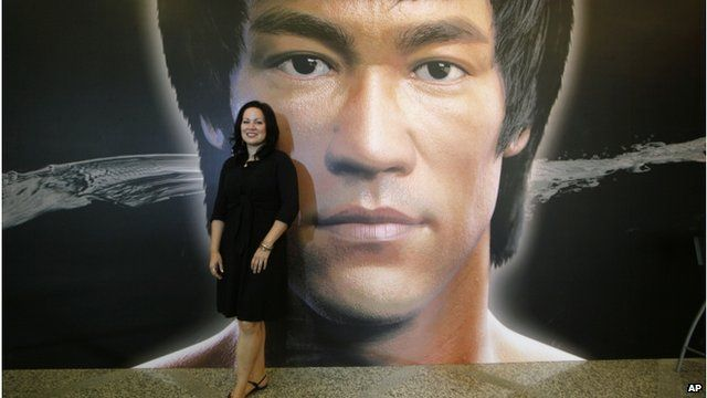 """Shannon Lee, daughter of the late Kung Fu star Bruce Lee, poses in front of a promotional poster for Lee""""s memorial exhibition"""