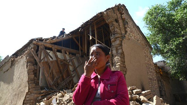 Resident stands in front of a house damaged by the earthquake in China