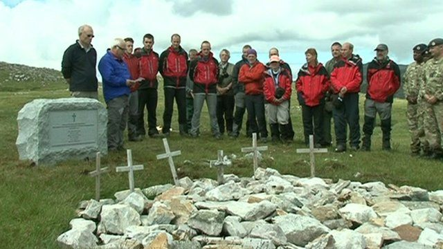 People gathered around a new granite memorial near Lochinver