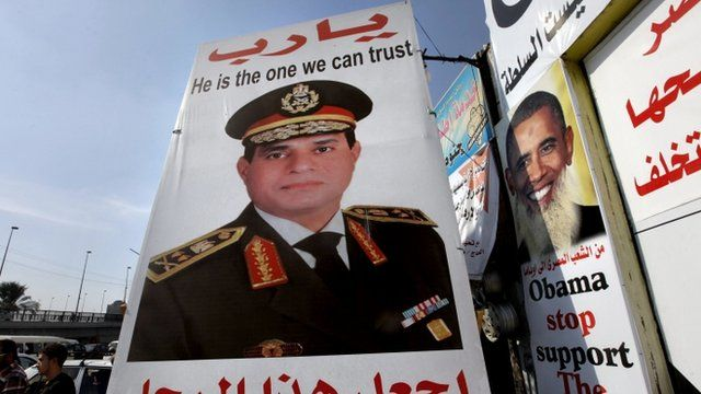 "Egyptians walk behind a banner depicting U.S President Barak Obama, right, and a banner supporting Egyptian Army Chief Lt. Gen. Abdel-Fattah el-Sissi, center, with Arabic that reads, ""God, keep this truthful honest man,"" in Cairo, Egypt"