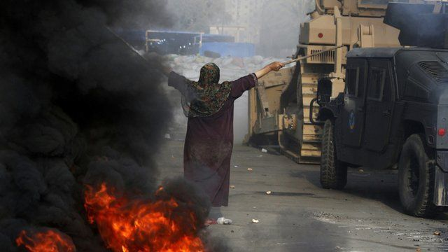 An Egyptian woman gestures in front of a military bulldozer
