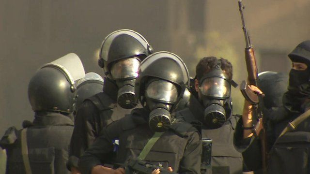 Security forces in Cairo, wearing gas masks and carrying guns