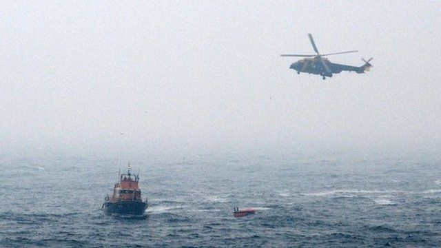 Rescuers approaching a liferaft from the crashed helicopter