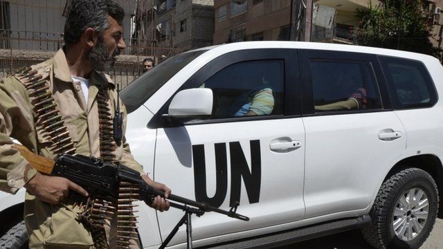 A Free Syrian Army fighter carries his weapon as he and fellow fighters escort a convoy of UN vehicle