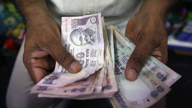 A man counts Indian Rupee currency notes at a shop in Mumbai