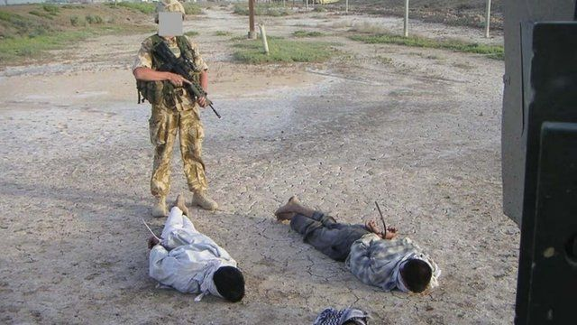 Detained Iraqis being guarded by a British soldier, as shown at the The Al-Sweady Inquiry