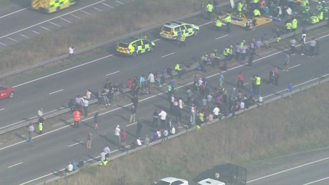 Aerial shot of people standing by the side of the road and emergency vehicles