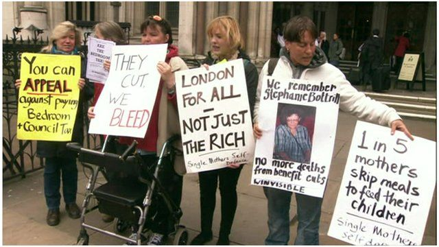 Women stand outside parliament with banners protesting the 'bedroom tax' policy