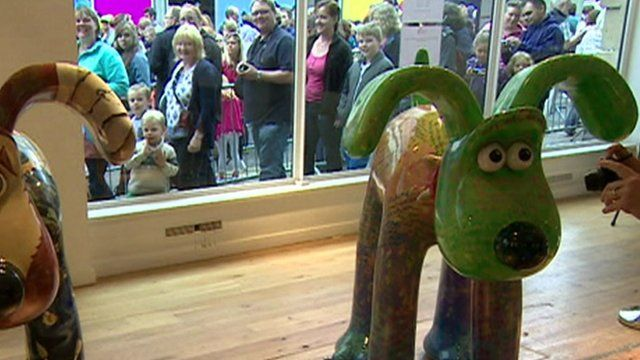 Gromit statues, with queues of people in window behind