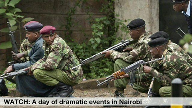 Armed police from the General Service Unit take cover behind a wall during a bout of gunfire, outside the Westgate Mall in Nairobi