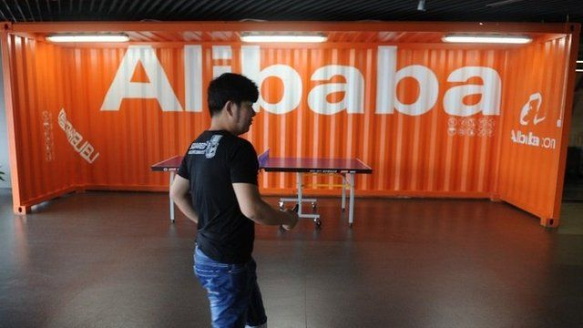 Employee walks past Alibaba sign
