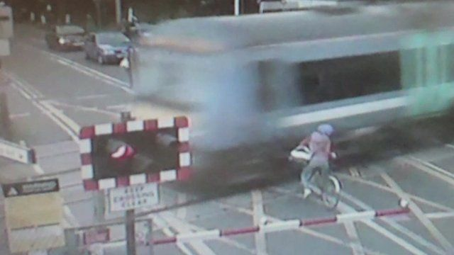 Woman on bike backing away from moving train