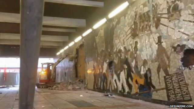 A digger pulls the mural down