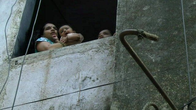 Family looking out of window of dangerous building