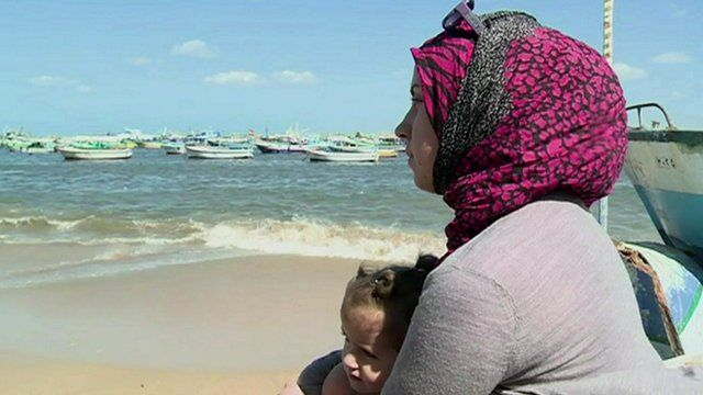 A Syrian refugee holds her daughter near the Alexandrian coast