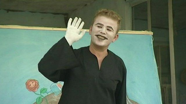 A mime actor waving to the audience.