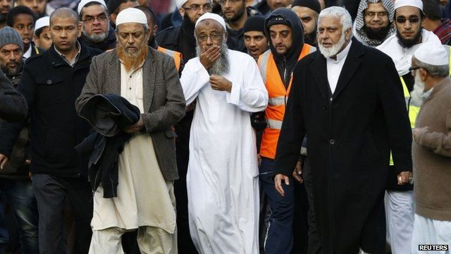 Sattar Taufiq walks with members of the community after funeral prayers for his wife and children at Spinney Hill Park in Leicester