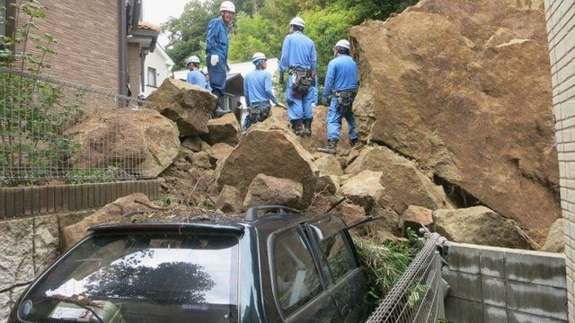 Fire fighters stand on rocks fallen from a cliff over a garage and a road in a residential area in Kamakura, southwest of Tokyo