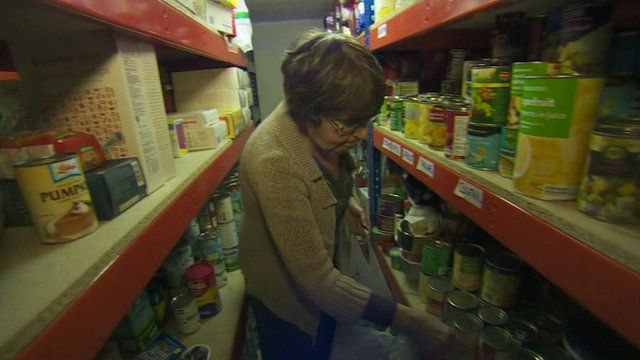 Food bank worker collecting and bagging tins of food