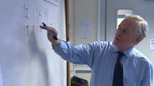 Maths teacher David Shrubbs writing on a board