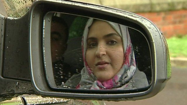 Women in reflection of car wing mirror