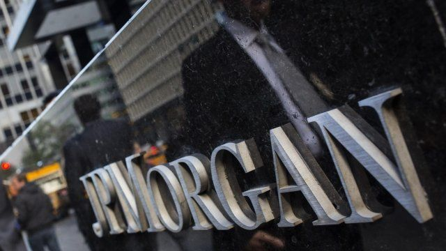People walking past reflected in JP Morgan sign