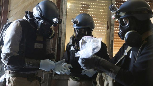 UN chemical weapons expert holds a plastic bag containing samples from one of the sites of an alleged chemical weapons attack in the Ain Tarma neighbourhood of Damascus in this August 29, 2013 file photo