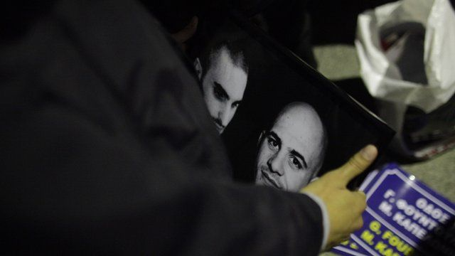 A supporter of the extreme right party of Golden Dawn, holds a picture with the images of Manolis Kapelonis, left, and Giorgos Foudoulakis, who were killed in a shooting